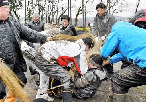わら束でたたかれながら、団子が詰まった俵を奪い合う若者たち=9日、福井市上細江町の粟嶋神社