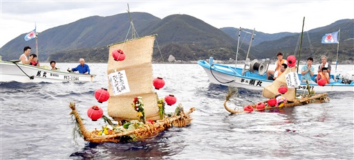 住民が手を合わせる中、海に送り出される精霊船=8月15日午後5時50分ごろ、福井県福井市白浜町沖