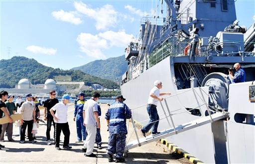原子力総合防災訓練で多用途支援艦「ひうち」に乗り込む住民。奥に見えるのは高浜原発3、4号機=8月26日午前10時5分ごろ、福井県高浜町の内浦港