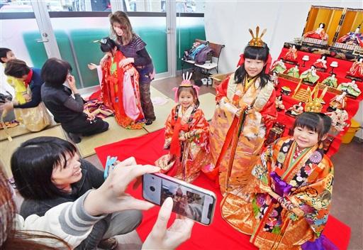 色鮮やかな十二単をまとい写真に収まる子どもたち=16日、福井市のハーツ志比口店