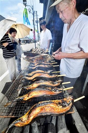 炭火で次々と焼かれ、香ばしい煙を上げる半夏生サバ=7月1日、福井県大野市の大亀屋