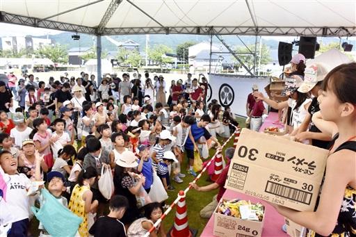丸岡古城まつりのオープニングイベントでまんじゅうまきを楽しむ子どもたち=8月11日、福井県坂井市丸岡体育館横のふれあい広場