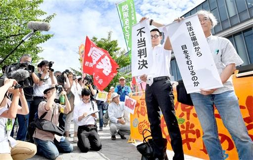 判決言い渡し直後、「不当判決」などと書かれた垂れ幕を掲げる原告団=7月4日午後3時すぎ、金沢市の名古屋高裁金沢支部前