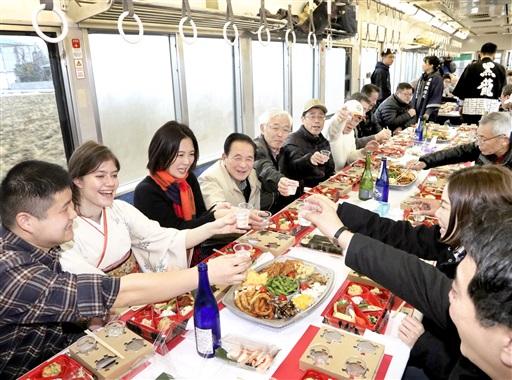 えちぜん鉄道の電車内で日本酒と料理を楽しむ参加者=2月2日、福井県勝山市内
