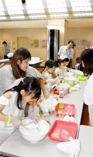 紙おむつに水を掛け吸水力を確かめる子どもら=8月23日、美浜町佐田の原子力安全システム研究所