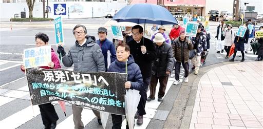 「福島の原発事故は収束していない」と訴え行進する参加者=3月11日、福井県福井市大手3丁目