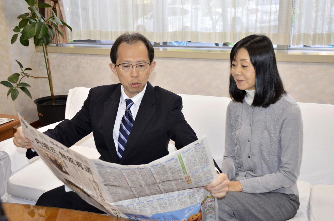 福島県知事選から一夜明け、当選を伝える新聞を広げる内堀雅雄氏=29日午前、福島市
