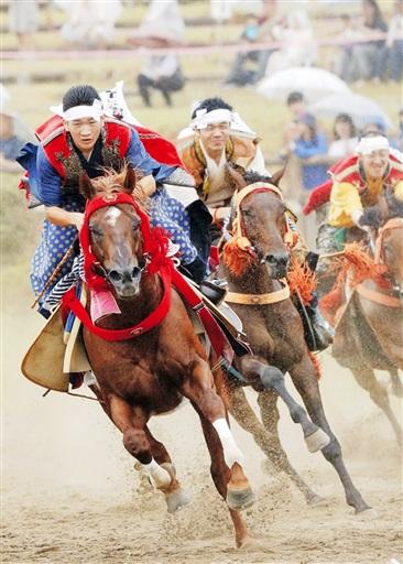 相馬野馬追の「宵乗り競馬」で疾走する陣羽織姿の騎馬武者たち=28日午後、福島県南相馬市