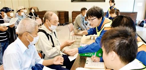 福井県おおい町職員らからヨウ素剤に見立てたあめ玉をもらう町民=8月26日、同町ふるさと交流センター